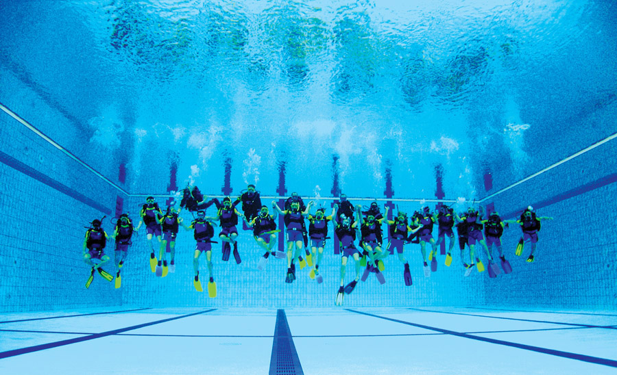 Long line of scuba divers mid water in the National Aquatic Center pool
